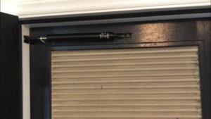 Door closer fully installed on top door rail
