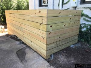 treated wood fence hiding air conditioning unit