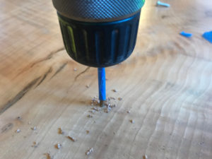 drilling into nice wood table with drill bit marked with painter's tape