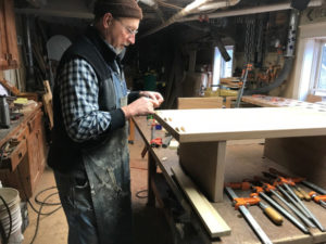 woodworker in woodworking shop setting glue biscuits