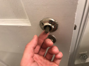 loose old door knobs removed show spindle shaft coming through door handle