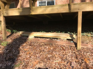 store leftover treated deck boards under porch on bricks