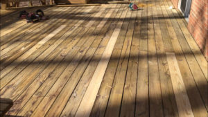 old rotted deck boards replaced with new treated deck board lumber