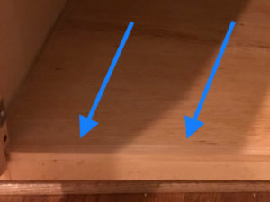 use custom pine trim piece to hide plywood edge in finished cabinet floor