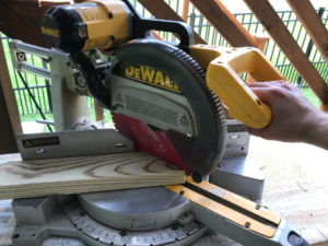 cutting treated 2x4 with a miter saw