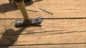 pulling loose deck nail with claw hammer