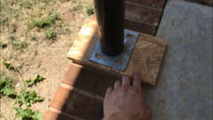 Position protective wooden blocks above and below post jack