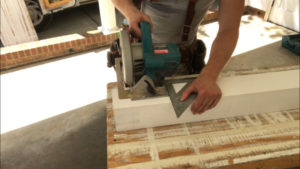 cutting the new wood porch column with circular saw and speed square