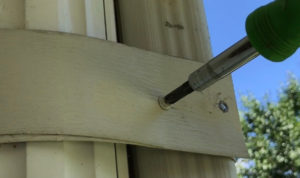 gutter screw being installed using a screwdriver