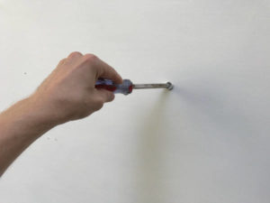 screwdriver punching hole in wall