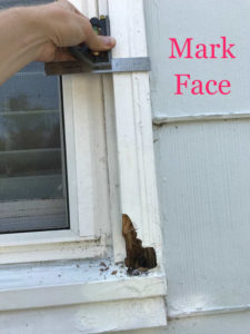 mark rotted brickmould face with combination square and pencil for window repair